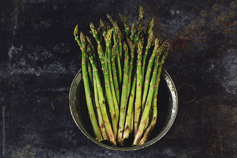 Raw asparagus in colander by Pixel Stories for Stocksy United
