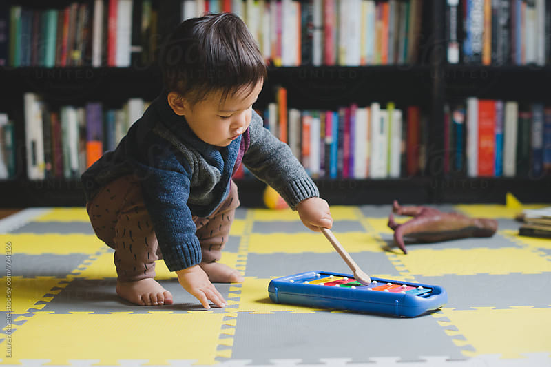Toddler playing with glockenspiel by Lauren Naefe for Stocksy United
