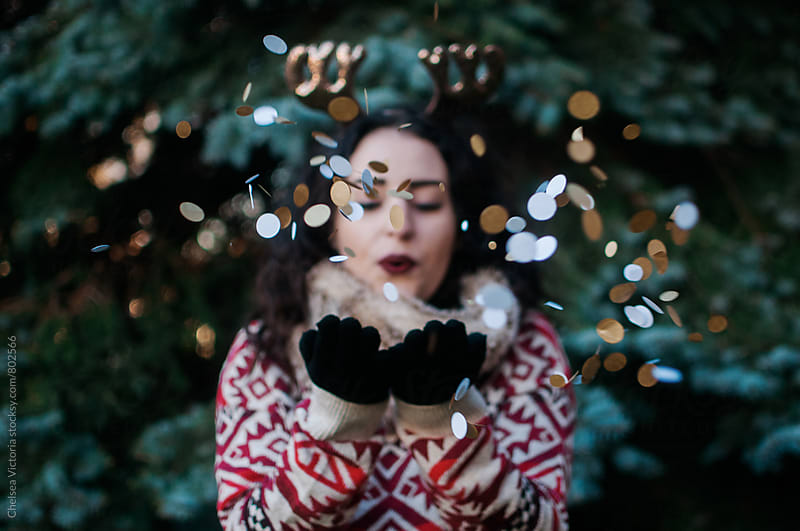 A young woman blowing christmas confetti in by Chelsea Victoria for Stocksy United