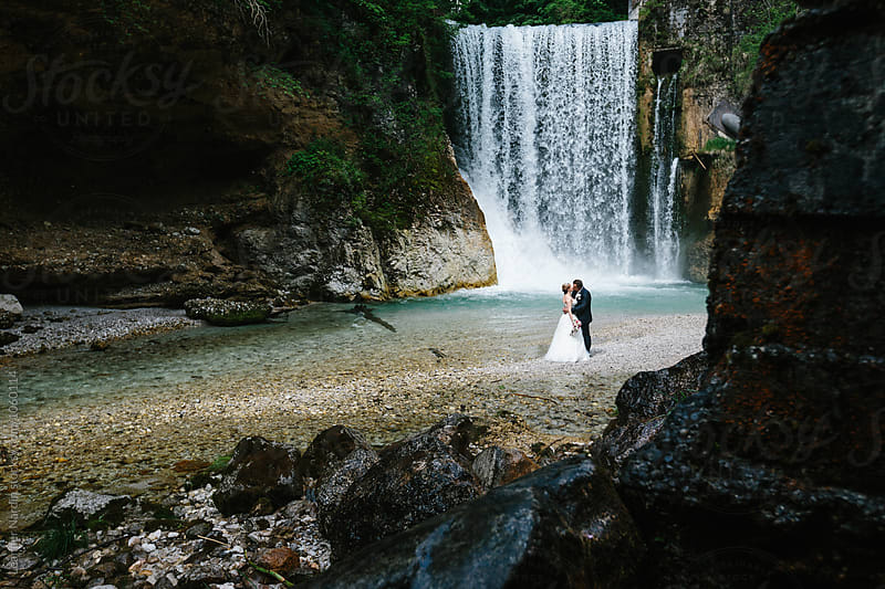 kissing bridal couple in front of a waterfall in deep forest  by Leander Nardin for Stocksy United