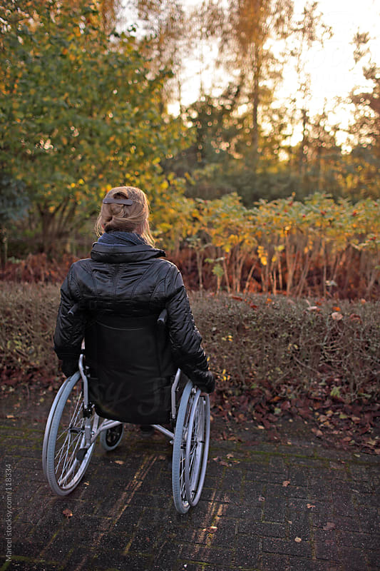 Woman in a wheelchair, looking at the sunset in a garden by Marcel for Stocksy United
