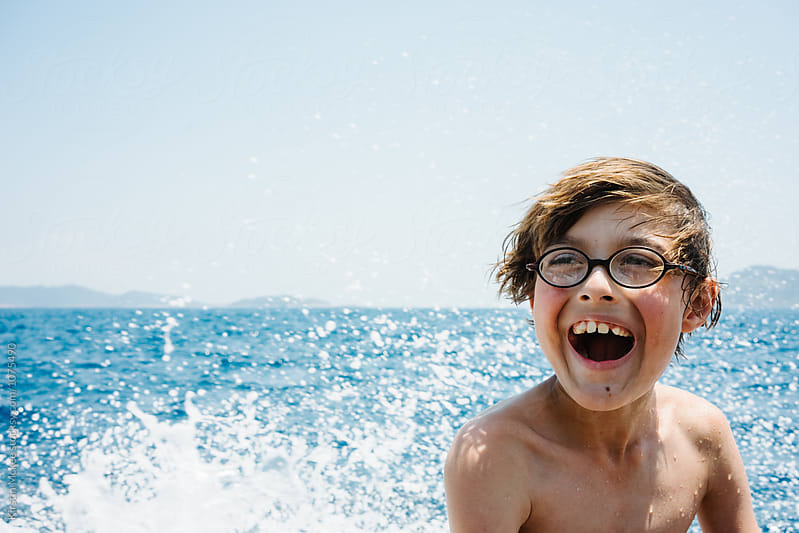 Boy grinning while travelling on the back of a motor boat by Kirstin Mckee for Stocksy United