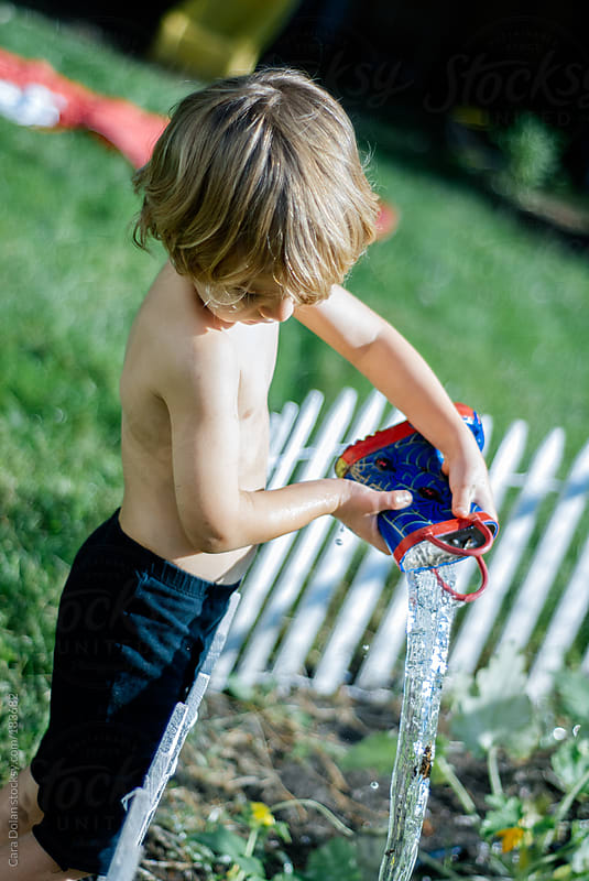 Toddler boy waters the garden with his rubber boot by Cara Dolan for Stocksy United