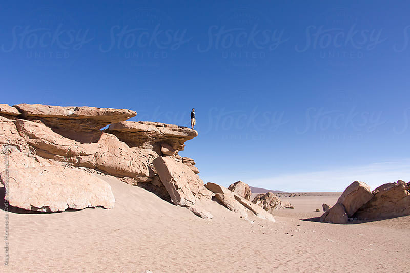 Young man standing on top of a rock ledge on desert landscape - Adventure travel by Alejandro Moreno de Carlos for Stocksy United