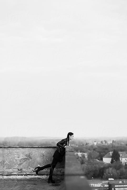 Young woman standing on top of the building by Jovana Rikalo for Stocksy United