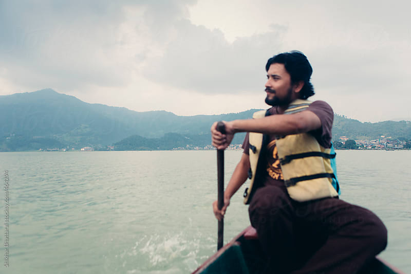 Young man rowing a boat. by Shikhar Bhattarai for Stocksy United