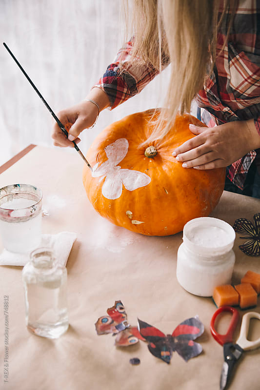 Woman painting pumpkin with brush and white gouache by T-REX & Flower for Stocksy United