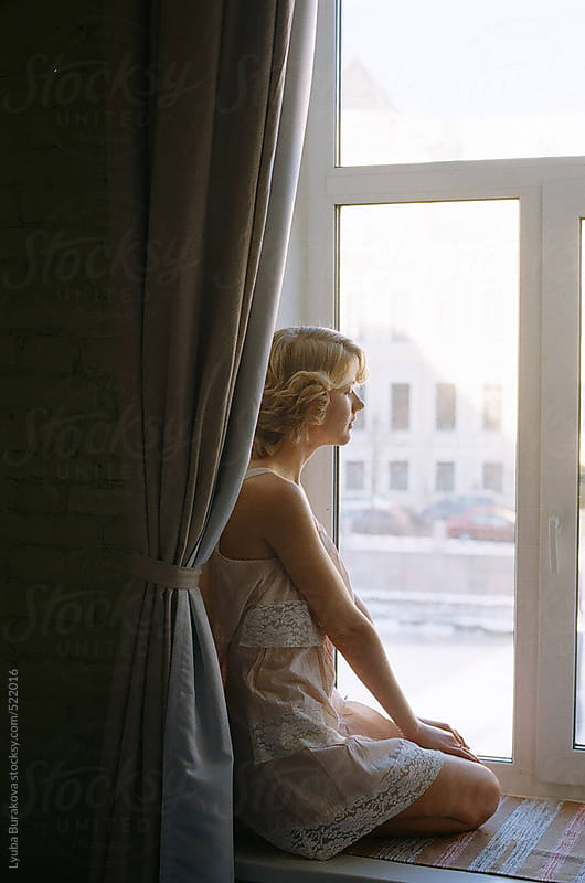 Young woman sitting on the window and looking away by Lyuba Burakova for Stocksy United