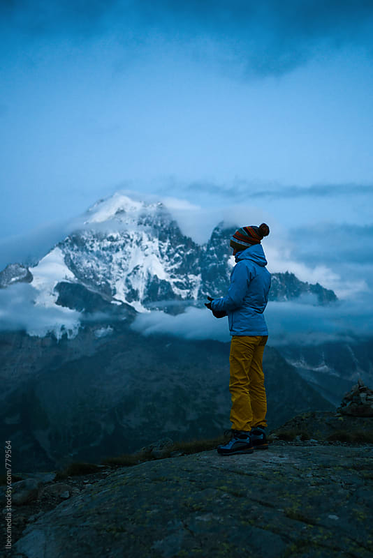 Hiker standing on a rock looking at mountain peaks in the twilight by RG&B Images for Stocksy United
