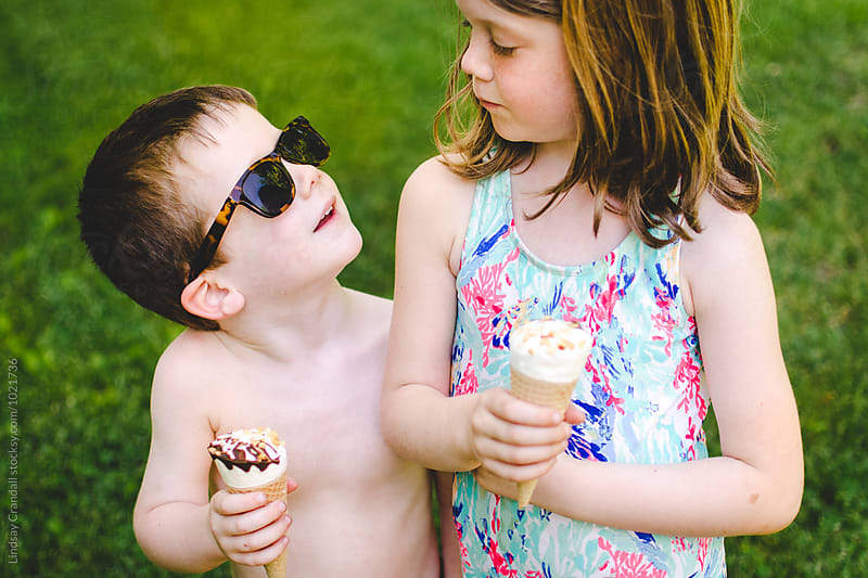 Boy and girl looking at each other while holding ice cream cones in summer by Lindsay Crandall for Stocksy United
