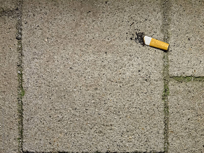 Finished cigarette stub on floor, concept: final cigarette by Melanie Kintz for Stocksy United