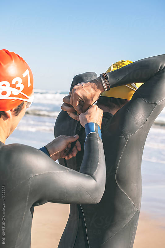 Two triathletes clothing wetsuit. Ready for swim. by BONNINSTUDIO for Stocksy United