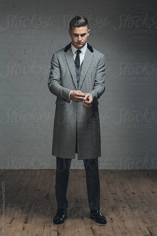 A handsome man in a long black and white coat fixing his cuffs by Ania Boniecka for Stocksy United
