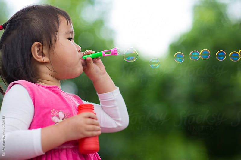 lovely little asian girl blowing bubble  by cuiyan Liu for Stocksy United