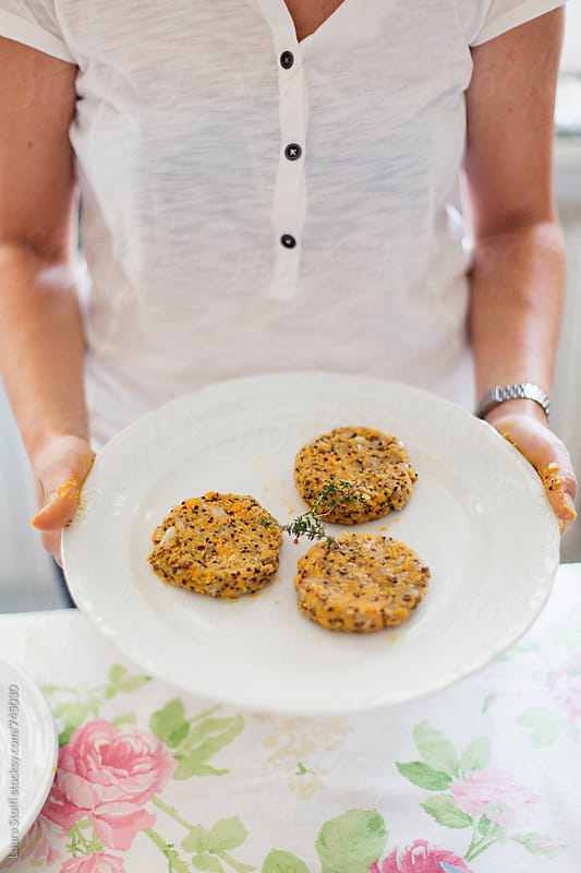 Young woman holding a dish with freshly made quinoa and sweet potatoes burgers by Laura Stolfi for Stocksy United