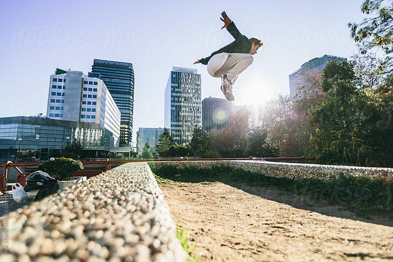 Man making a leap over a wall during a parkour training in a city by Inuk Studio for Stocksy United