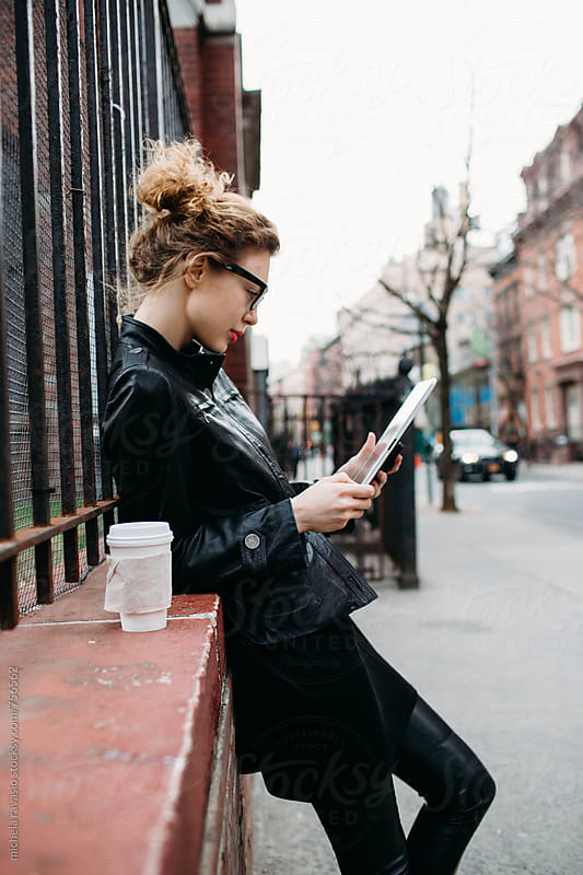 Business woman using her digital tablet outdoors by michela ravasio for Stocksy United