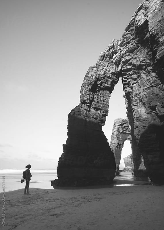 Young woman looking at the natural arches in the Beach of the Cathedrals by ACALU Studio for Stocksy United