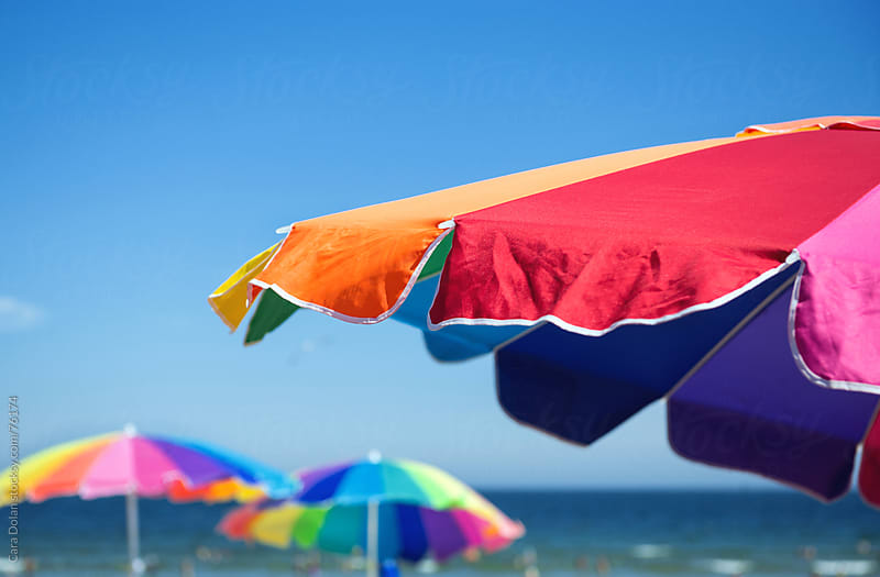 A trio of colorful beach umbrellas by Cara Dolan for Stocksy United