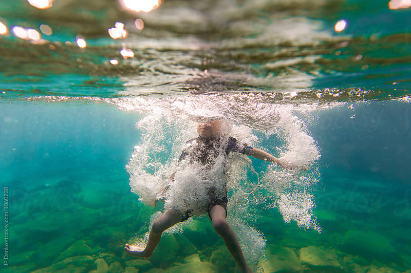 Underwater Splash of Boy Jumping Into Summer Lake From Water Trampoline At Cottage on Sunny Day by JP Danko for Stocksy United