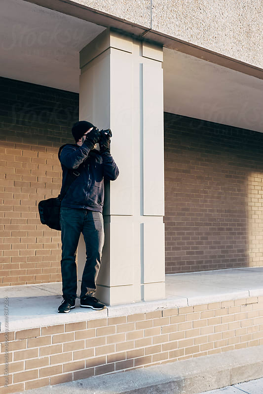 Man taking photographs near modern buildings by Paul Edmondson for Stocksy United