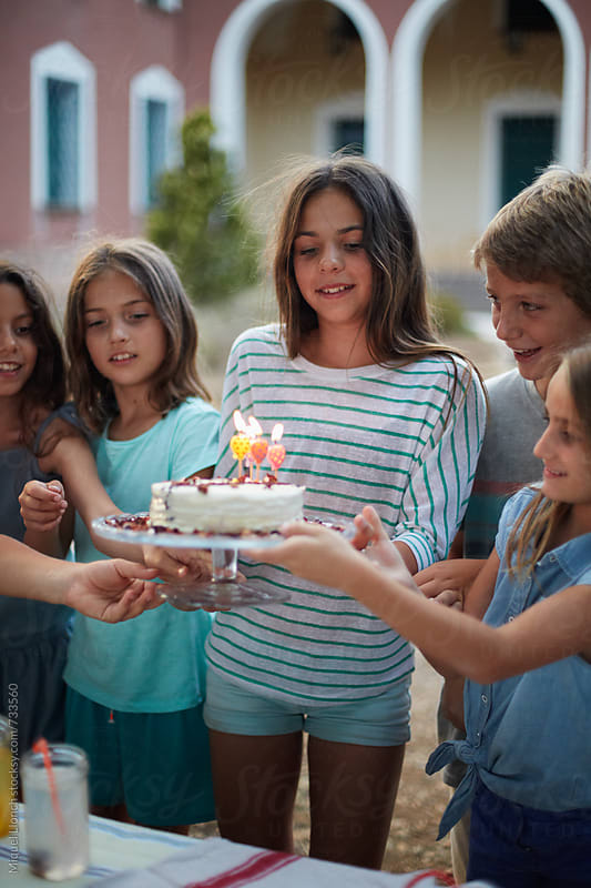 Young girl and friends carrying a cake for celebrating a birthday by Miquel Llonch for Stocksy United