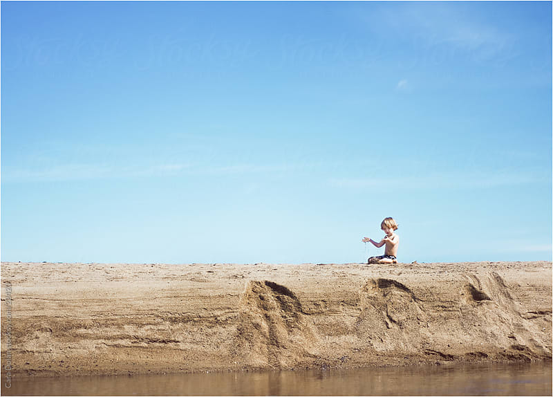 Boy plays with sand at the beach by Cara Slifka for Stocksy United
