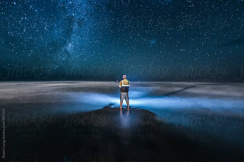 Fishing under a milky way night sky by Robert Lang for Stocksy United