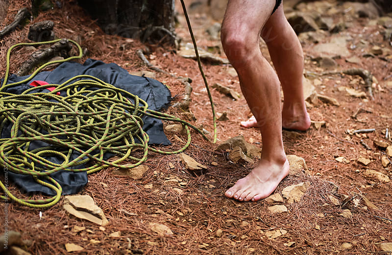 Legs of barefoot man standing in dirt with rock climbing rope by Matthew Spaulding for Stocksy United
