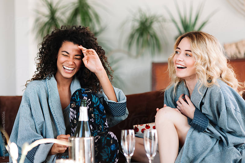 Friends drinking champagne and laughing by Kayla Snell for Stocksy United