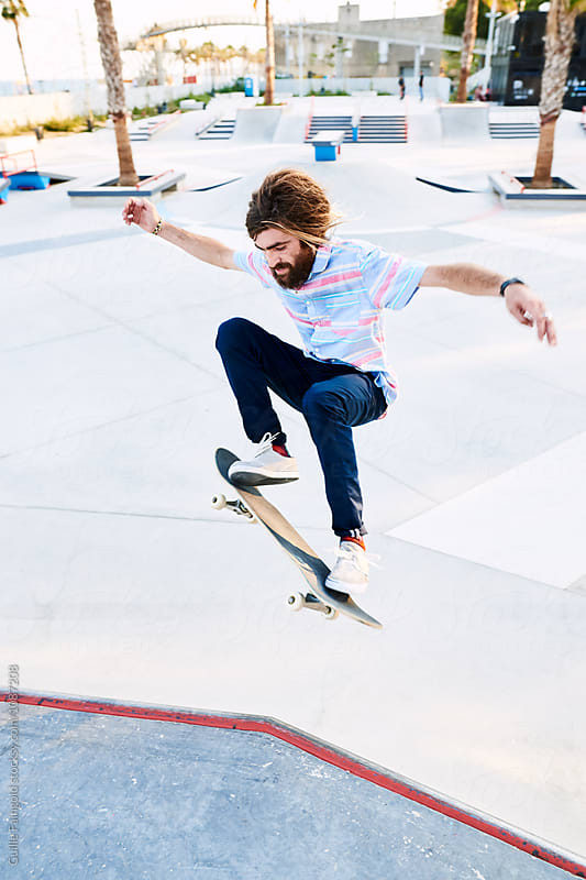 Bearded skater performing trick  by Guille Faingold for Stocksy United