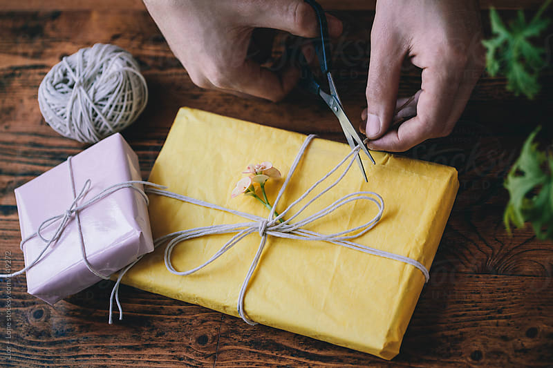 Man's hands cutting twine tied around a gift by Lior + Lone for Stocksy United