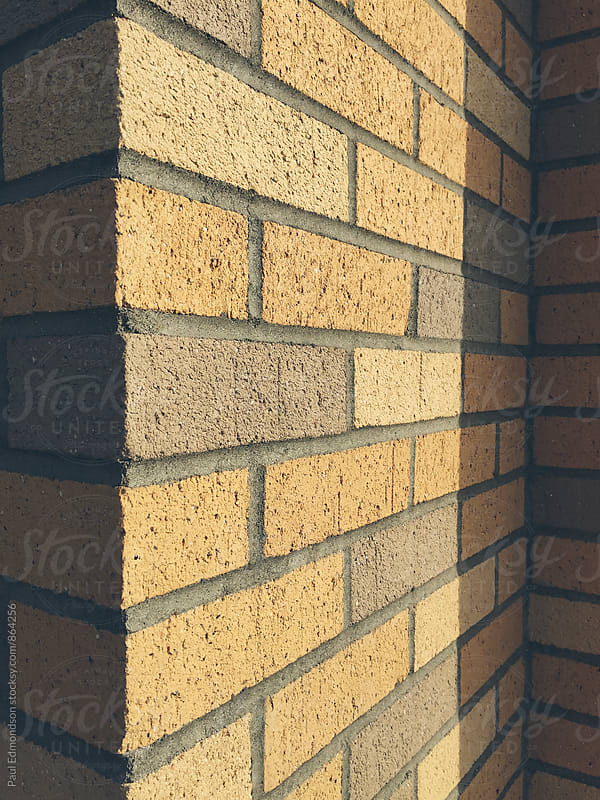 Beige and brown brick wall, casting shadow by Paul Edmondson for Stocksy United