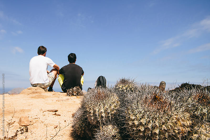 Two men on a desert with cactus on foreground. Adventure travel by Alejandro Moreno de Carlos for Stocksy United