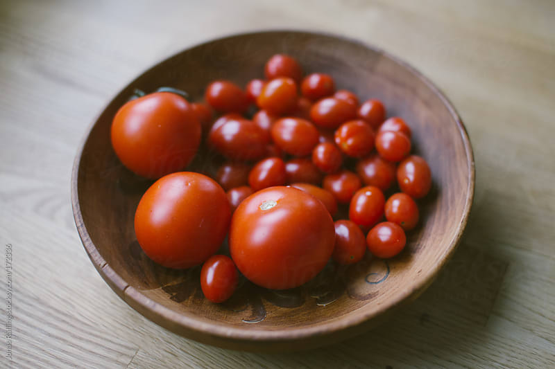 Tomatoes in a wooden bowl by Jonas Räfling for Stocksy United