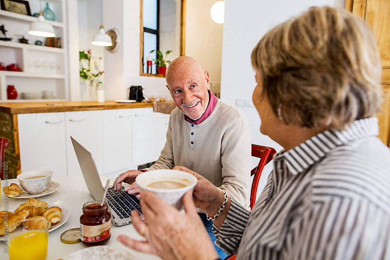 Elderly couple having a breakfast at home. by BONNINSTUDIO for Stocksy United