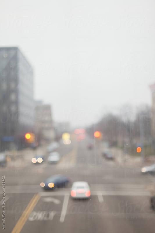 Out of focus view of city intersection through a dirty window by Amanda Worrall for Stocksy United