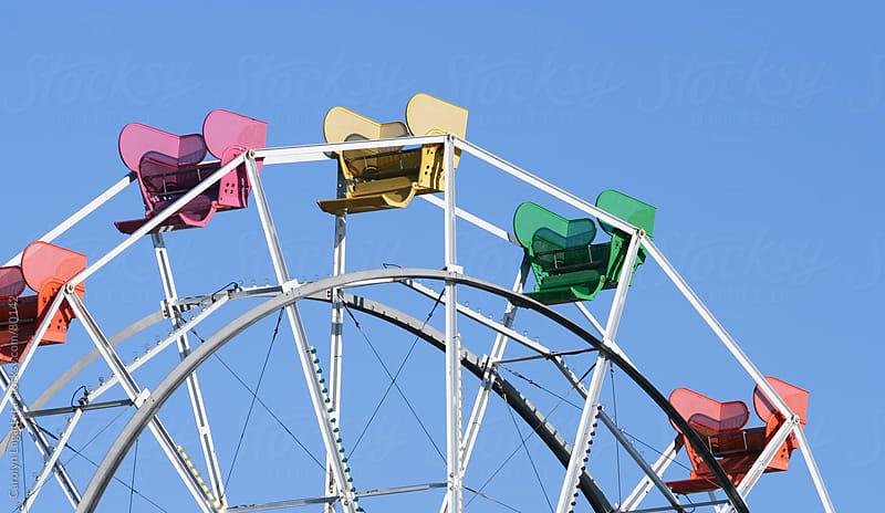 Colorful seats on the empty ferris wheel by Carolyn Lagattuta for Stocksy United