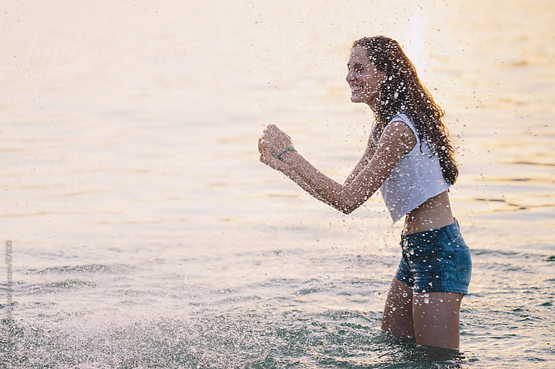 Young woman under spray of water by michela ravasio for Stocksy United