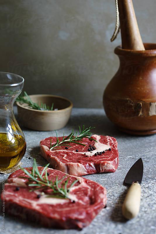 Ribeye steaks being prepared for cooking. by Darren Muir for Stocksy United