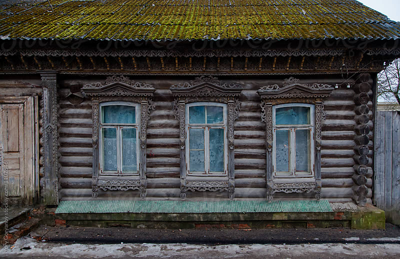 Facade of an old Russian house with carved and carved architraves windows by Yury Goryanoy for Stocksy United
