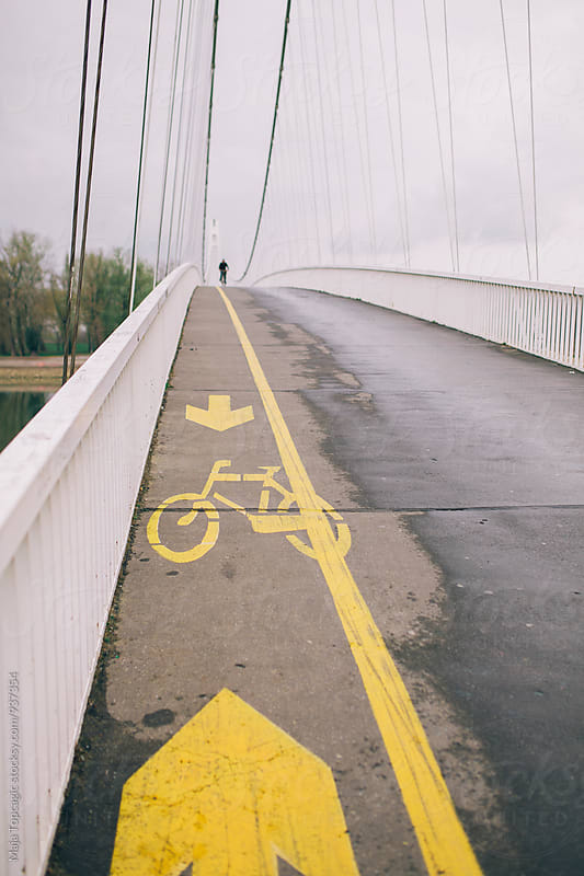 Bicyclist riding a bike on a bridge on a rainy day by Maja Topcagic for Stocksy United