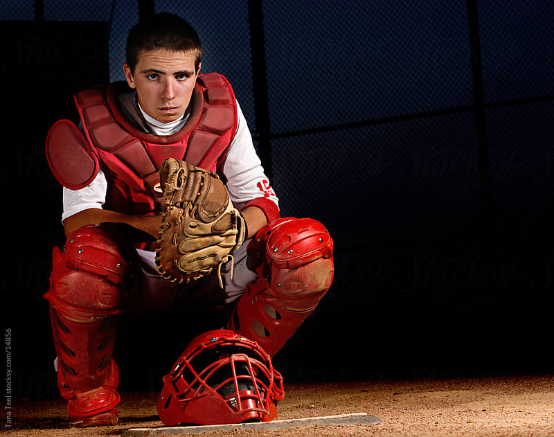 Baseball catcher behind homeplate.  by Tana Teel for Stocksy United