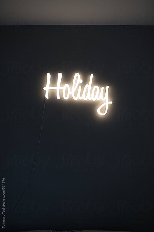 Holiday sign glowing in the dark by Tommaso Tuzj for Stocksy United