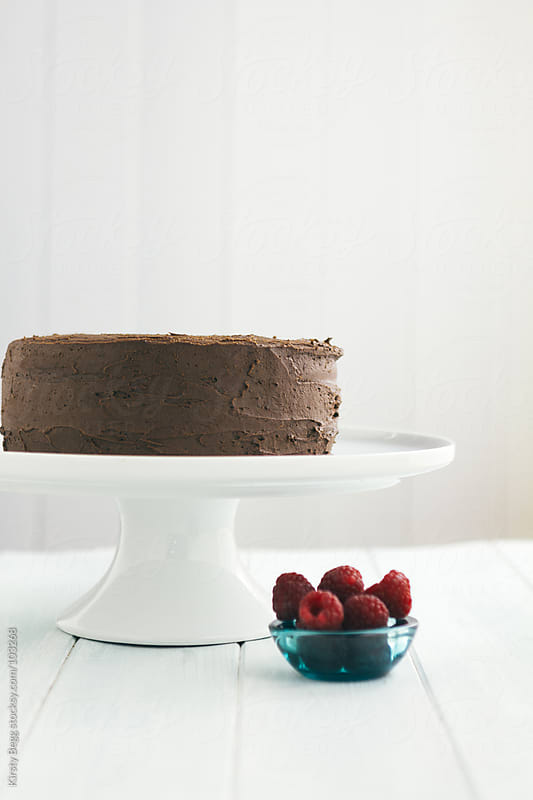 Chocolate buttercream  chocolate cake on white cake stand with r by Kirsty Begg for Stocksy United
