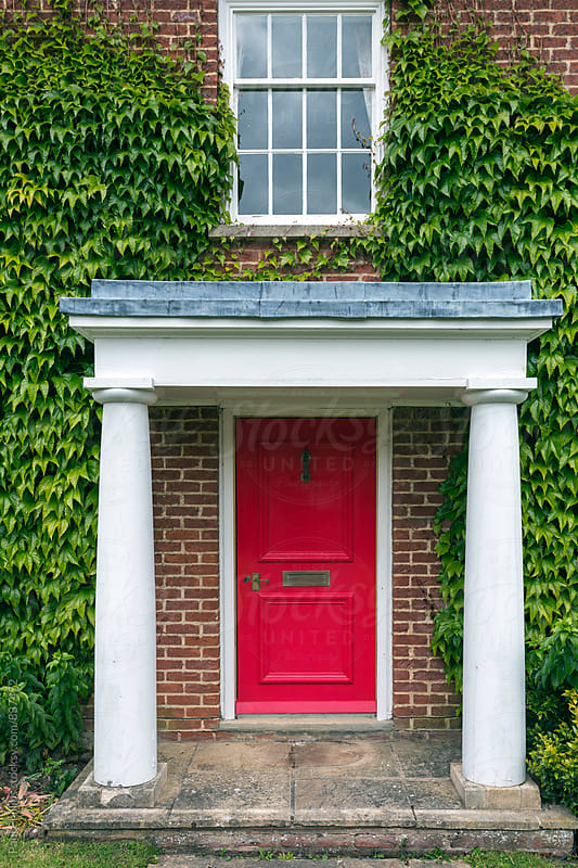 Red front door behind two pillars. Ivy either side. by Paul Phillips for Stocksy United