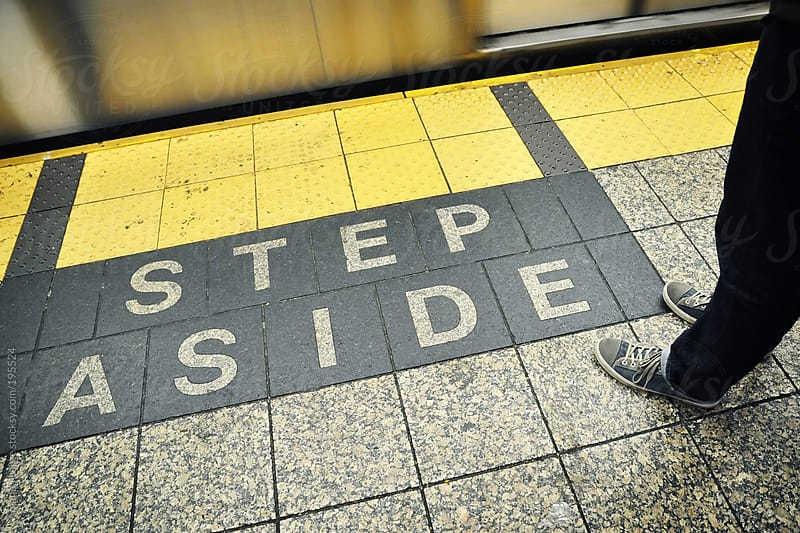 Man standing by a 'Step Aside' sign in the subway by Amanda Large for Stocksy United