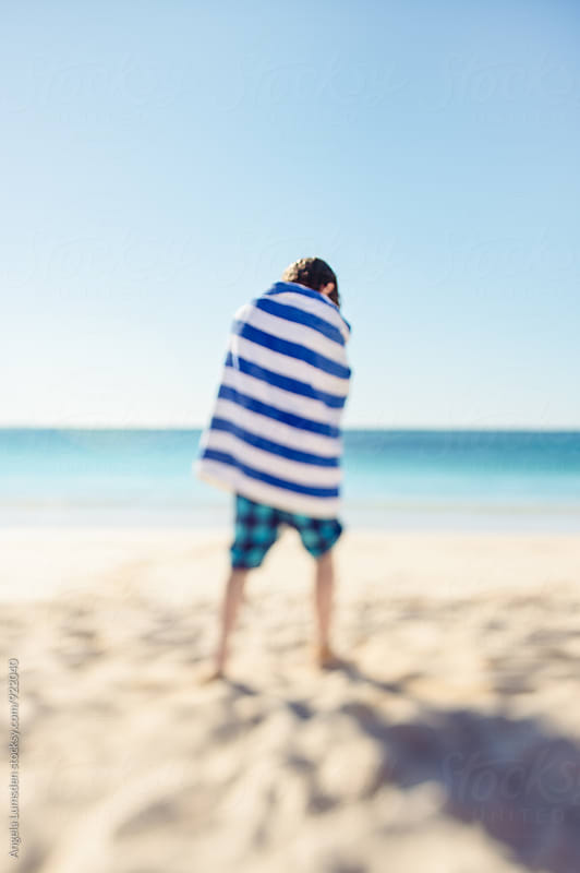 Boy wrappped in a towel at the beach on a sunny day by Angela Lumsden for Stocksy United