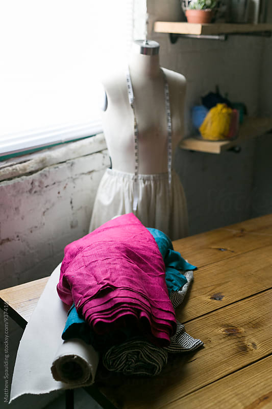 Textiles and cloth on table in designer's studio by Matthew Spaulding for Stocksy United