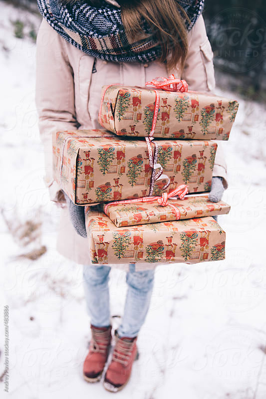 Girl holding an armful of gifts by Andrey Pavlov for Stocksy United